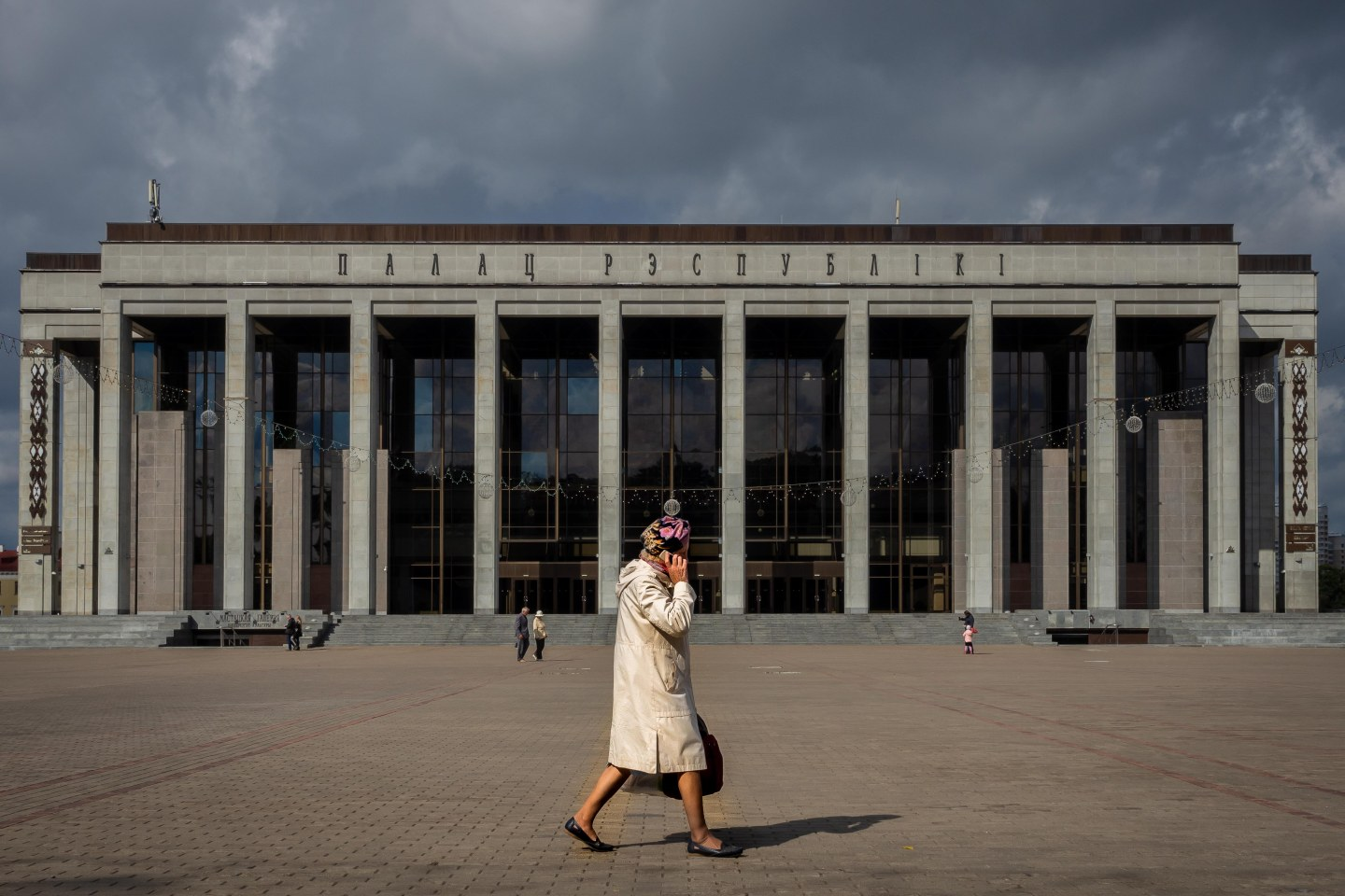 Woman walking cross October Square, Minsk, Belarus.