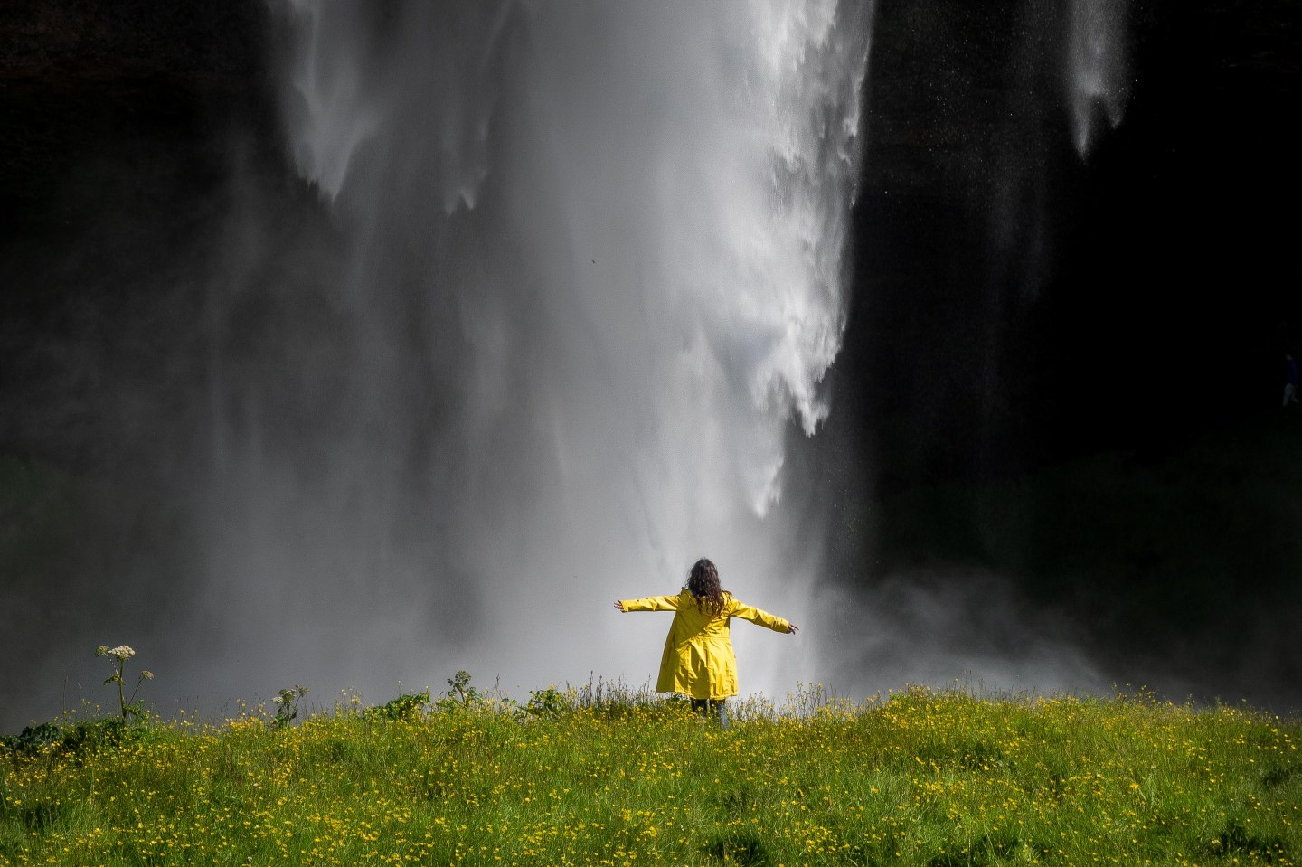 A girl standing under the waterfall, Seljalandfoss, Iceland.