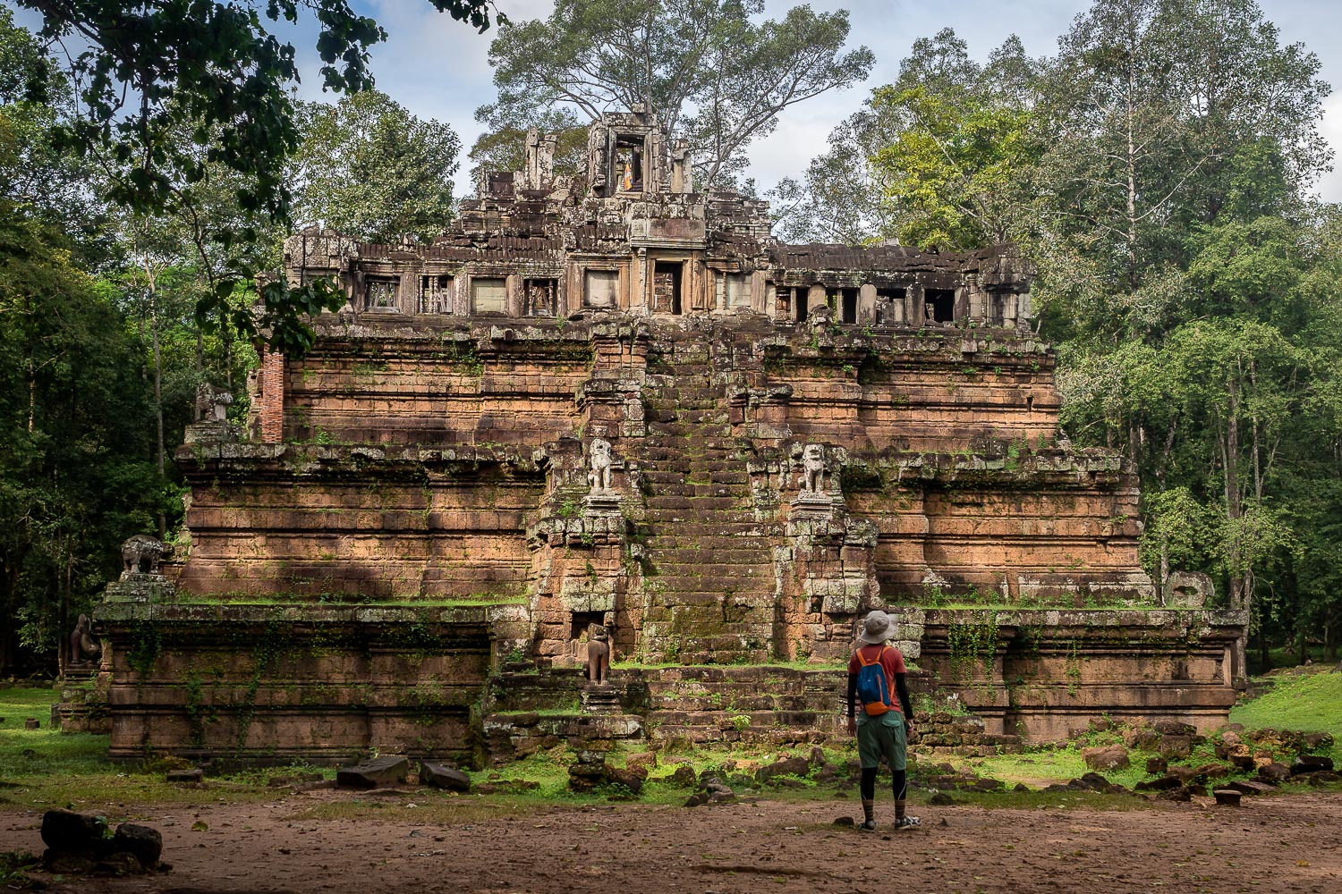 A man stands in front of the Phimeanakas temple, Angkor, Cambodia.