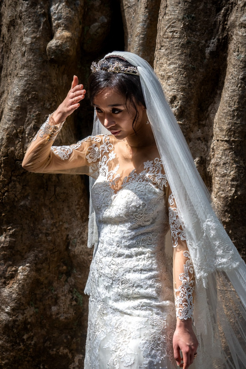 Bride shelter her face from the sun, Ta Phrom, Angkor, Cambodia.