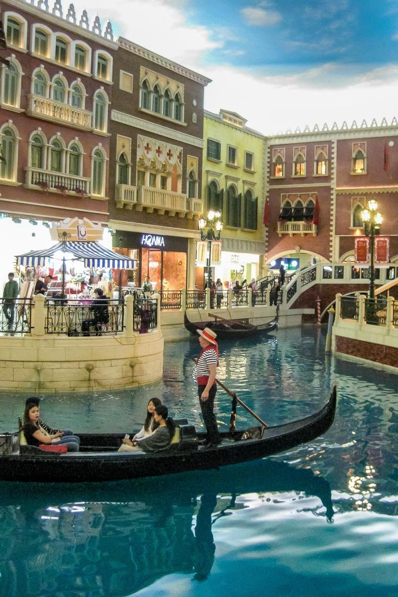 Guests riding a gondola at the Venetian Casino, Macau, China.