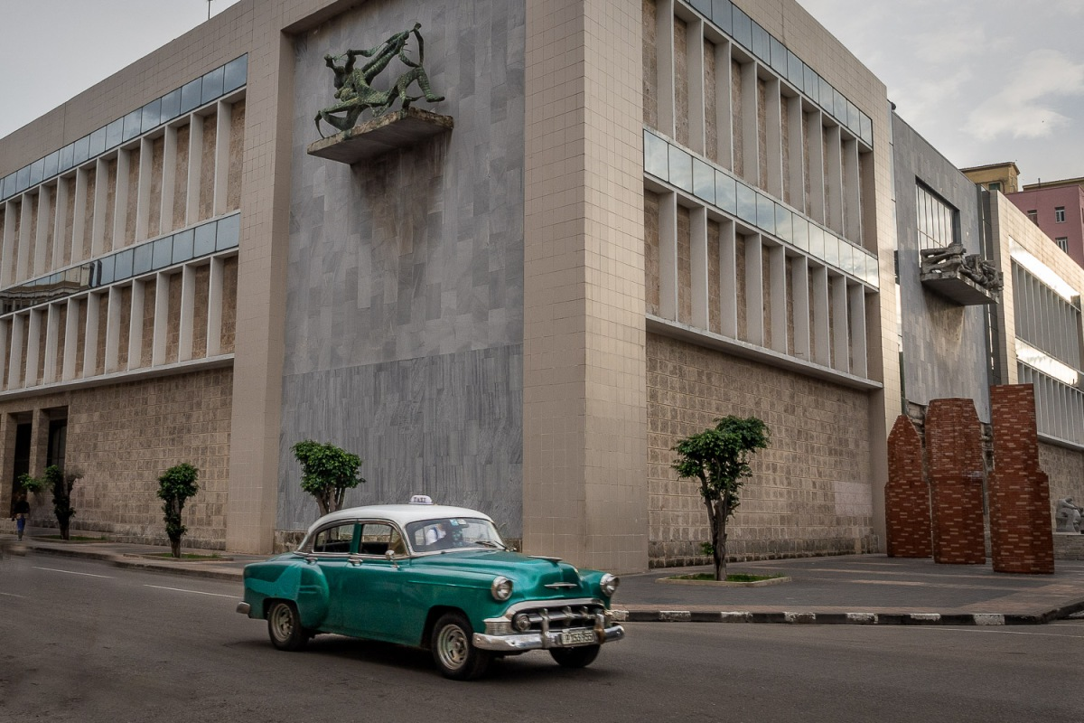 Car passing a public building, Havana, Cuba.