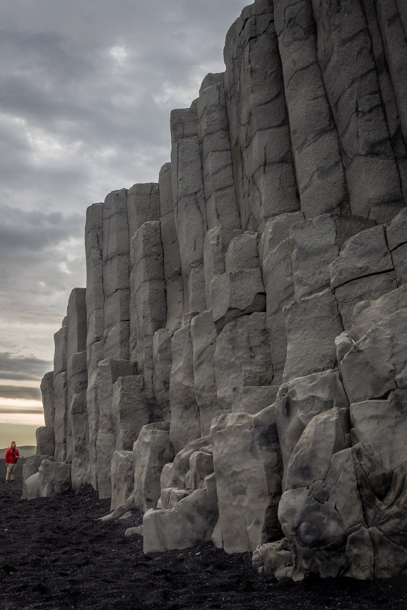Man standing below a giant rock formations, Reynisfjara, Iceland.