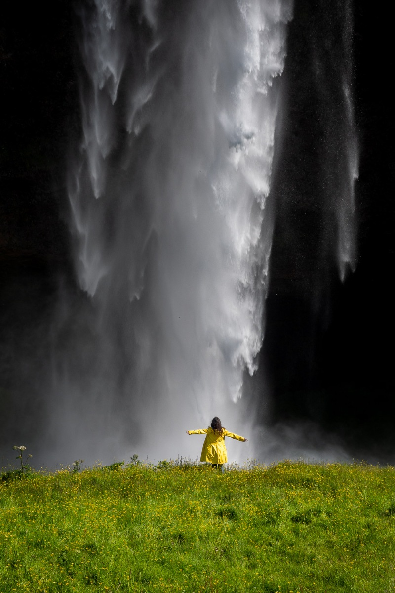 Girl standing under a waterfall, Seljalandfoss, Iceland.