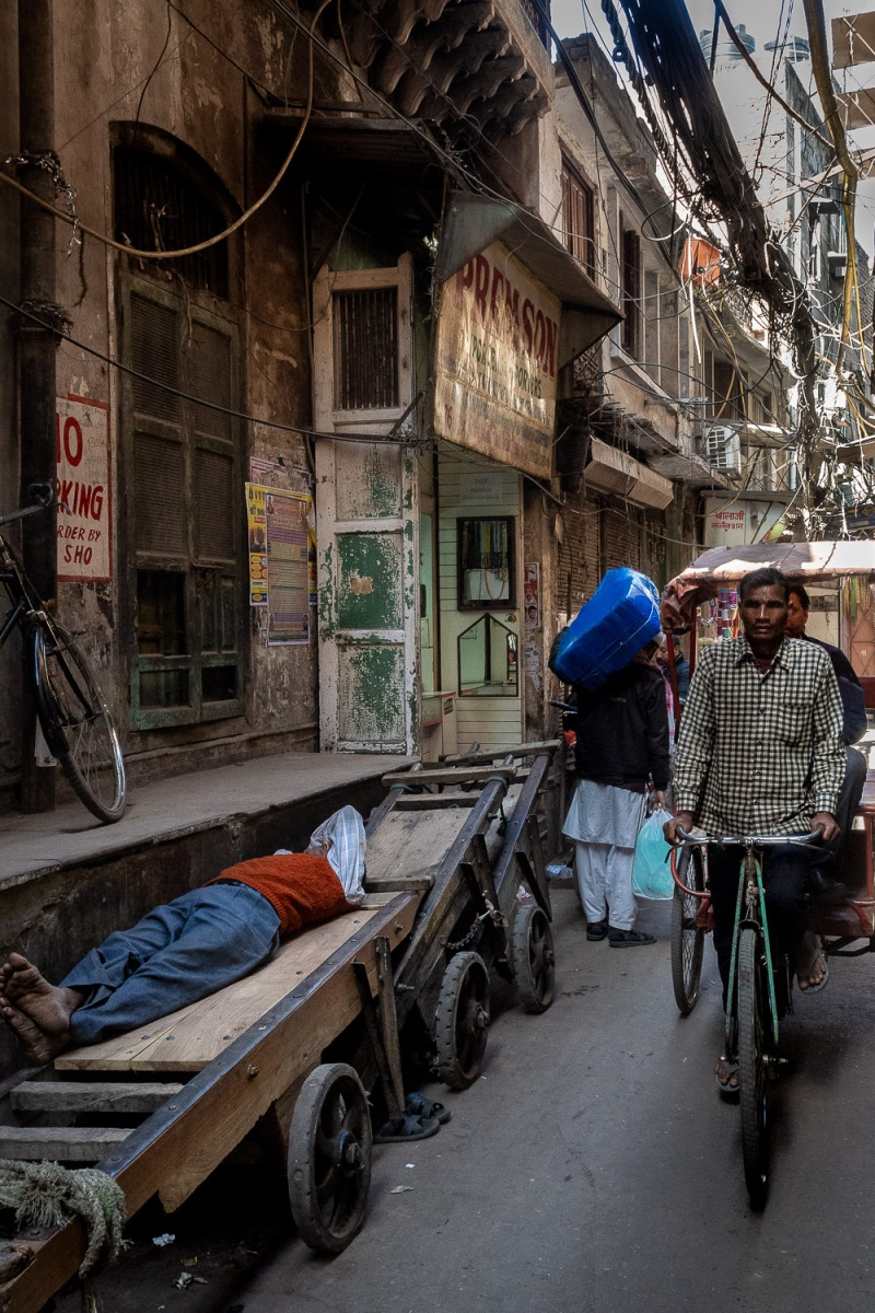 Man sleeping on a wheelbarrow, Old Delhi, India.