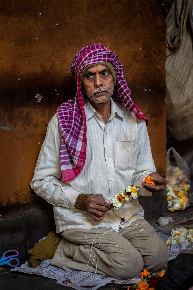 Man making flower decorations, Old Delhi, India.