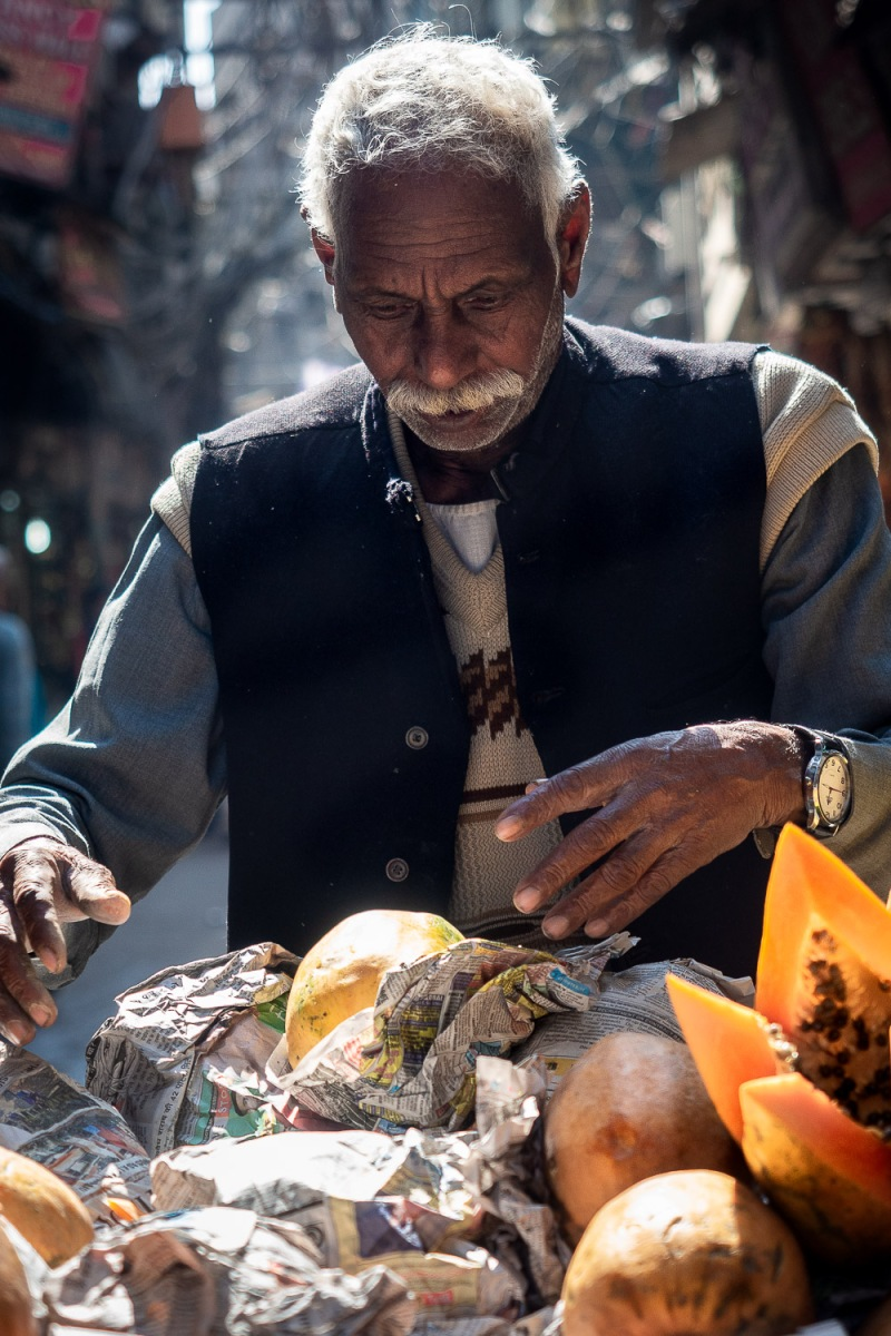 Man selling papayas wraped in newspaper, Old Delhi, India.