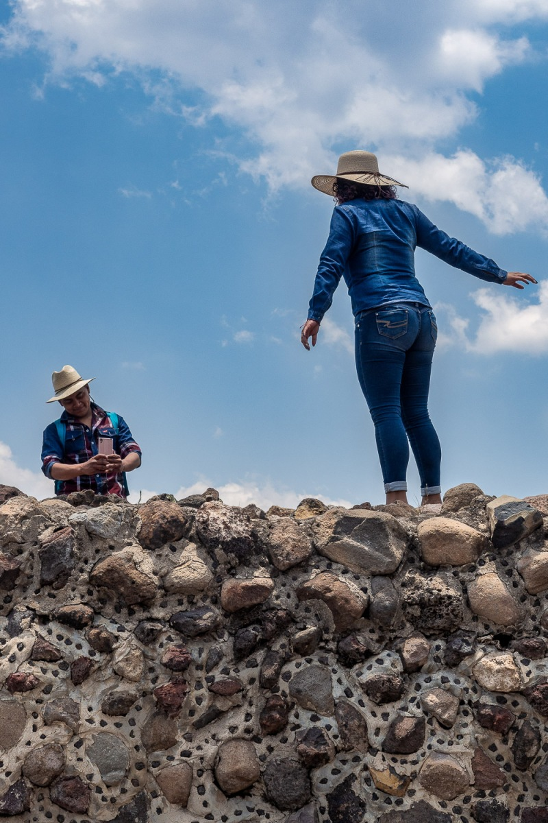 Woman photographed on a stone wall, Teotihuacan, Mexico.