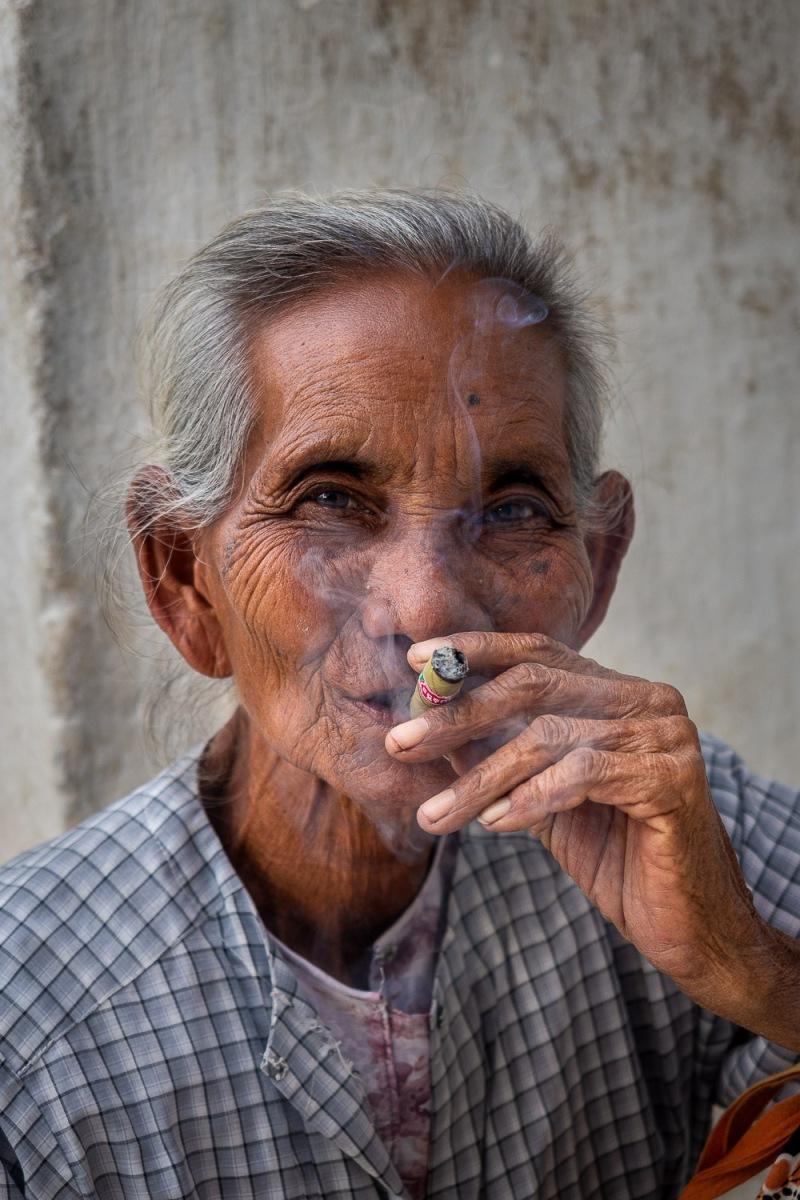 Woman smoking a cigar, Mandalay, Myanmar.