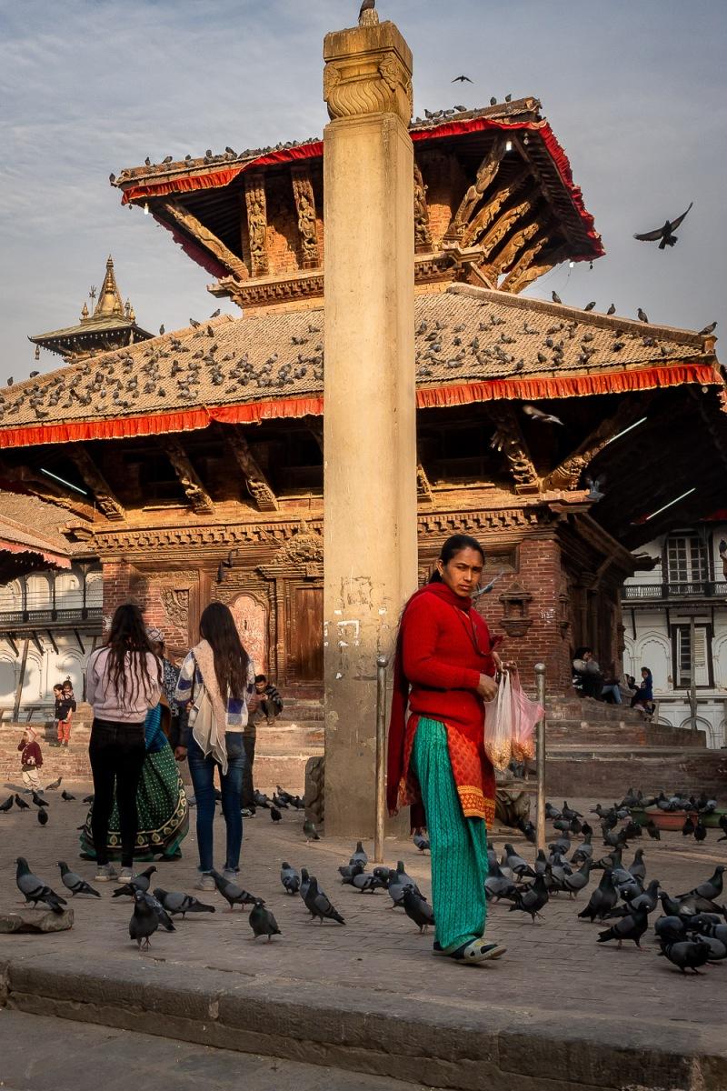 Woman feeding birds at Durbar Square, Kathmandu, Nepal.