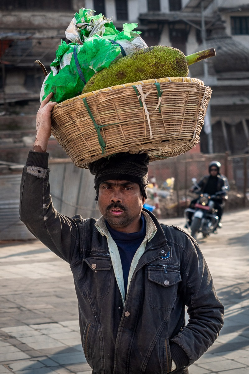 Man carrying durian fruits on his head, Kathmandu, Nepal.