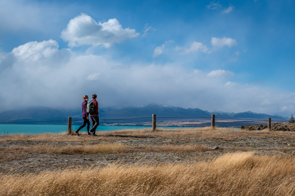 Couple walking along Lake Pukaki, Canterbury, New Zealand.