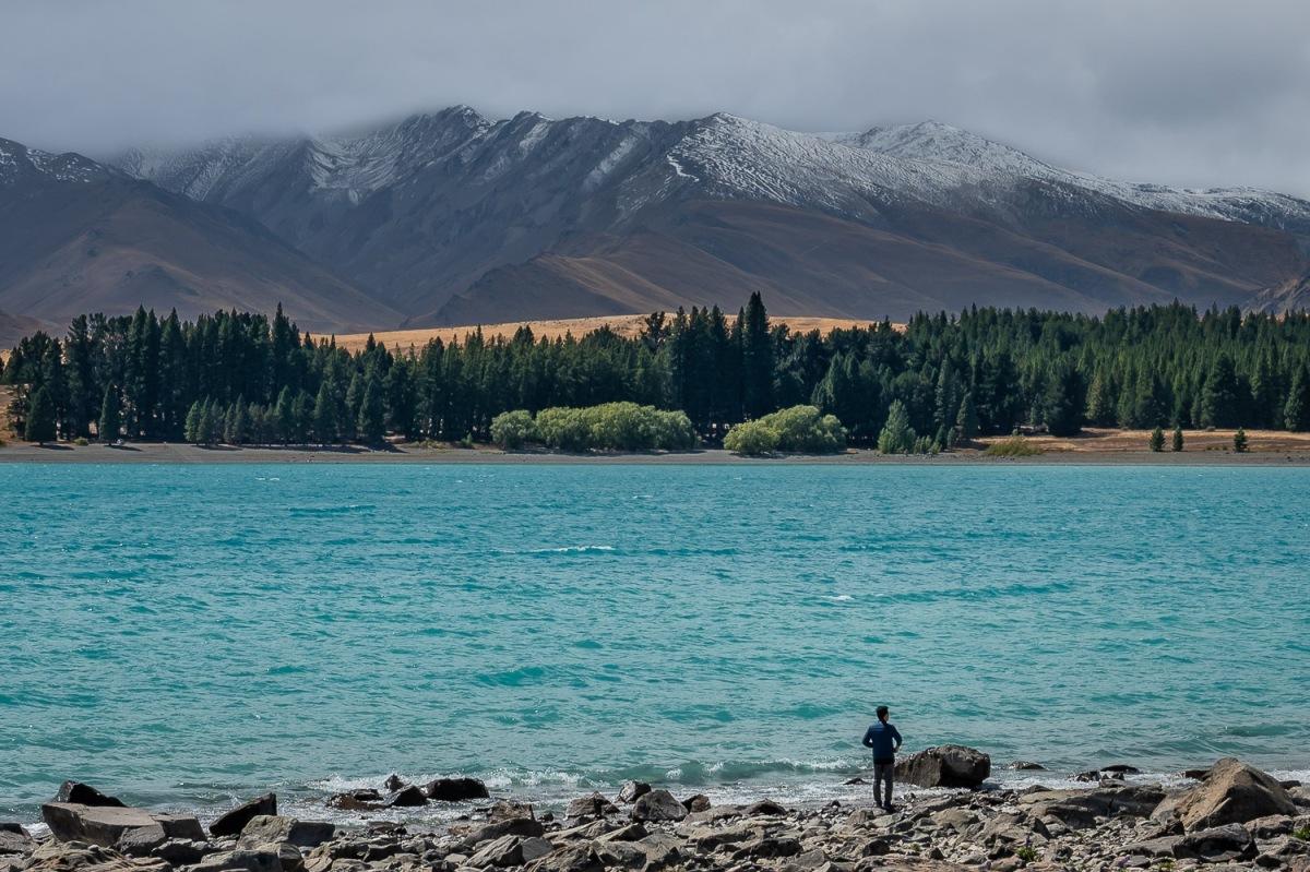 Man standing on the shore of Lake Tekapo, Canterbury, New Zealand.