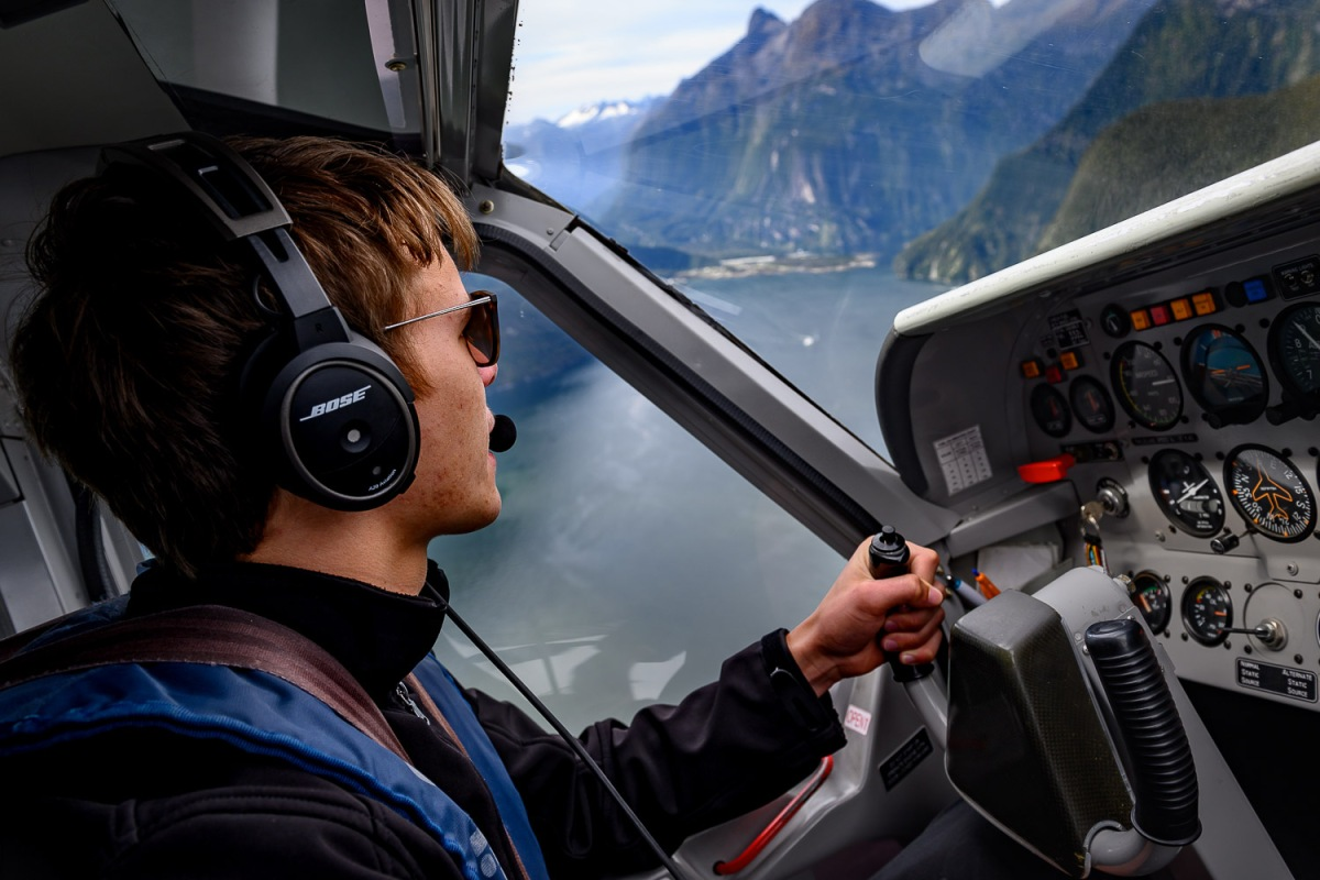A young pilot navigating through the mountains, Milford Sound, New Zealand.