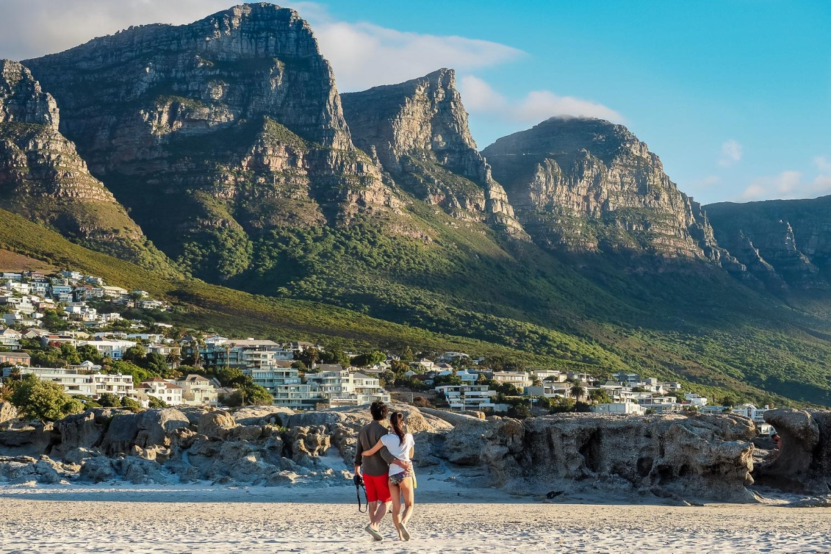 Couple walking cross the beach, Camps Bay, South Africa.