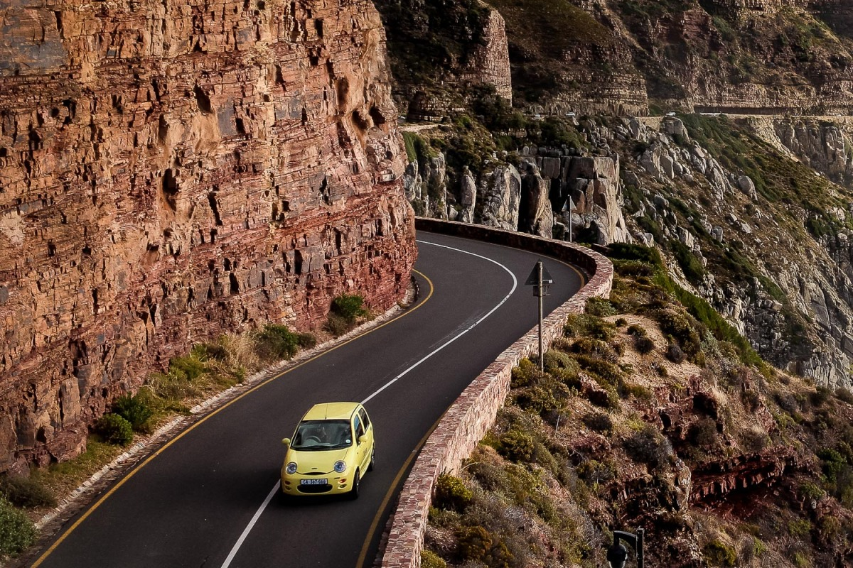 A car navigating the winding road, Chapman's Peak Drive, South Africa.