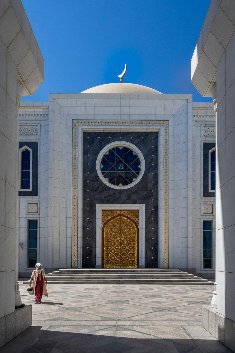 Woman passing the Ruhy mosque, Ashgabat, Turkmenistan.