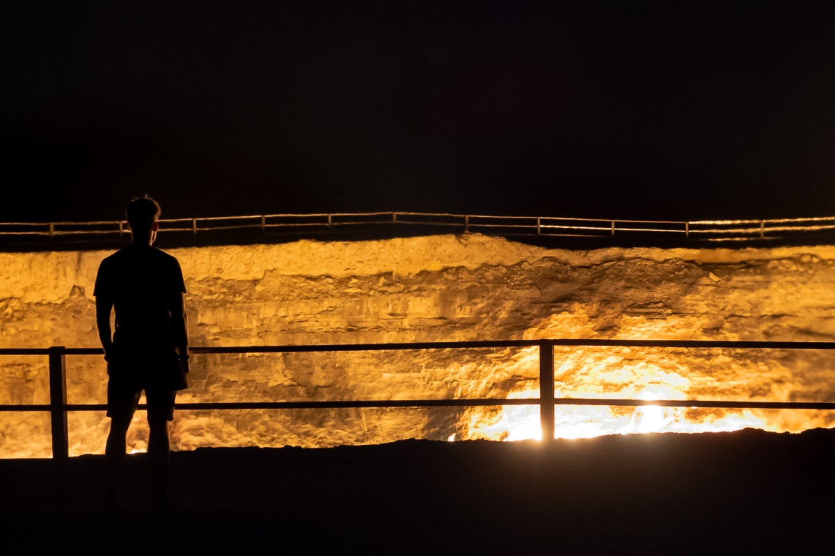 Man standing at the Darvaza gas crater, Karakum Desert, Turkmenistan.