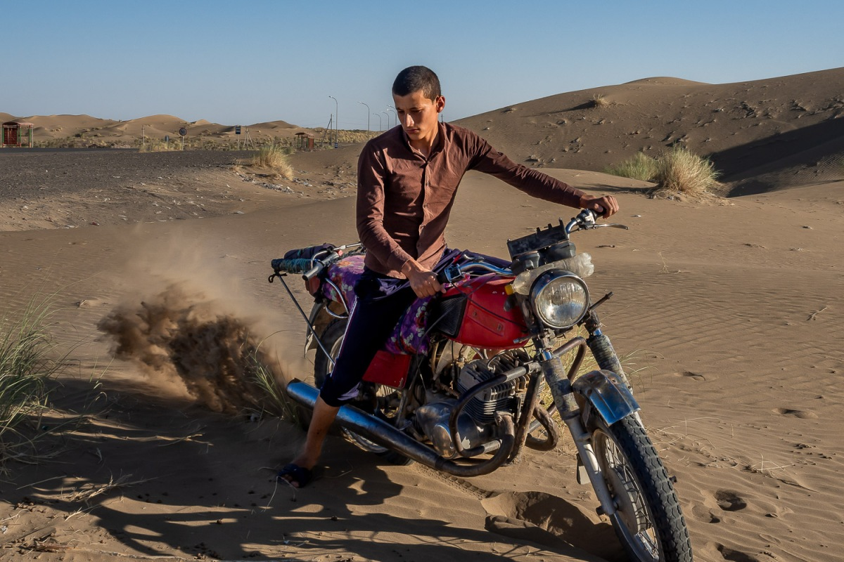 Boy burning his motor cycle on the sand dunes, Karakum Desert, Turkmenistan.