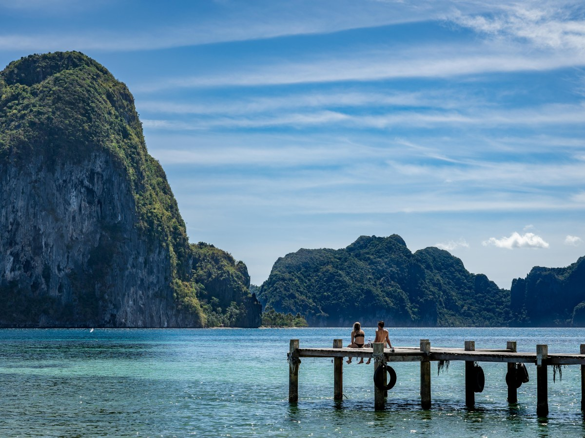 Couple on Marimegmeg Beach, El Nido, Palawan, the Philippines.